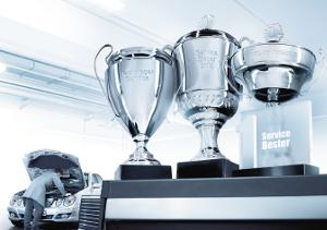 Pokale vor einem Mercedes